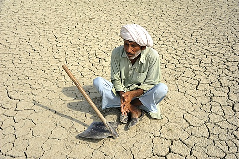 Farmer sitting on dried loamy soil, Basti Lehar Walla village, Punjab, Pakistan, Asia