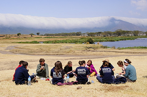 Tourists picnicing in front of the cloud covered edge of the Ngorongoro-crater, Ngorongoro Conservation Area, Tanzania, Africa