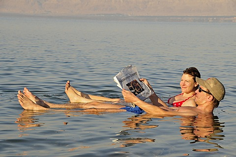Tourists reading the newspaper in the Dead Sea near Suwaymah, Jordan, Middle East, Orient