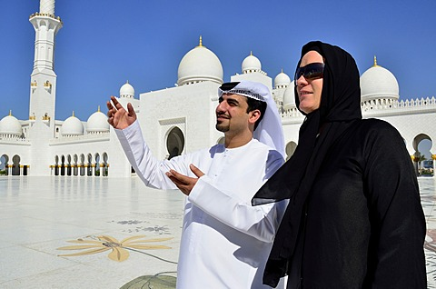 Local man giving veiled tourist a tour of the Sheikh Zayed Mosque, Abu Dhabi, United Arab Emirates, Arabian Peninsula, Asia