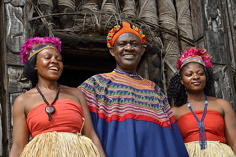 King Fon Abumbi II, head of one of the traditional kingdoms in north west Cameroon, in front of the Achum sanctuary at his seat of power with two of his favourite wives, Bafut Palace, near Bamenda, Cameroon, Central Africa, Africa