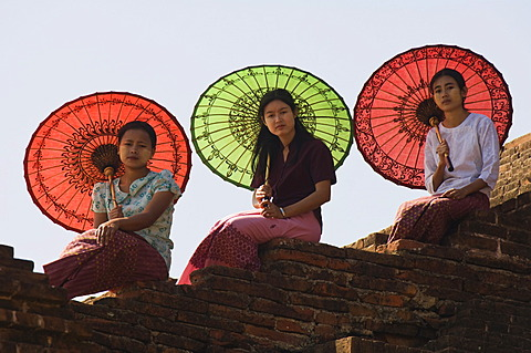 Young Burmese women with coloured parasols sitting on a temple wall, Bagan, Myanmar - 832-369219
