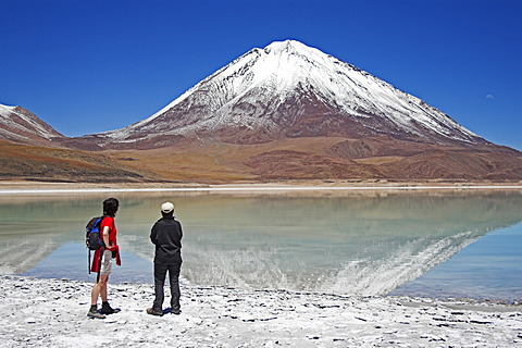 Women standing at the Laguna Verde and Licancabur volcano, Bolivia near the border to Chile, South America