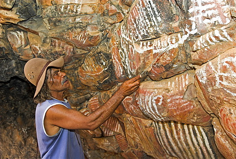 Australian aborigine explains rock paintings at Iga Wartha, Flinders Ranges, South Australia, Australia