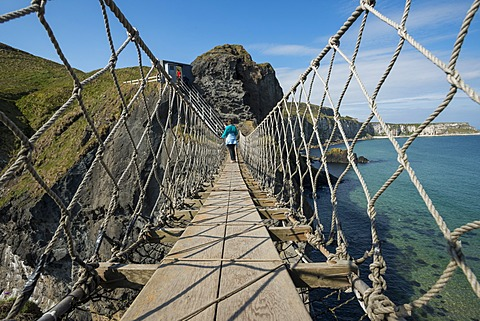 Carrick-a-Rede Bridge, woman crossing the suspension bridge, Moyle, Northern Ireland, United Kingdom, Europe