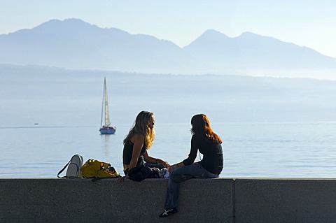 Young women chatting on a wall at Lake Geneva, Lac Leman, Ouchy, Lausanne, Switzerland
