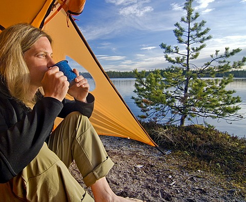 Woman sitting in front of a tent, looking into the distance and drinking out of a cup, Femundsmarka National Park, Femundsmark, Norway