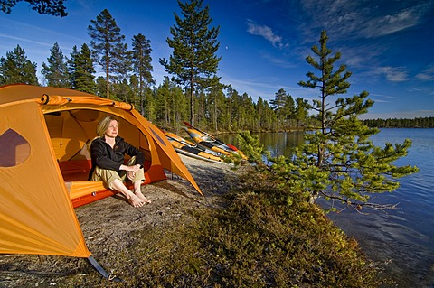 Woman sitting in front of a tent at a lakeside, looking into the distance, Femundsmarka National Park, Femundsmark, Norway