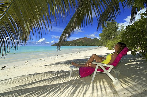 Young woman on deck chair, sleeping under palm trees, Praslin Island, Seychelles, Africa
