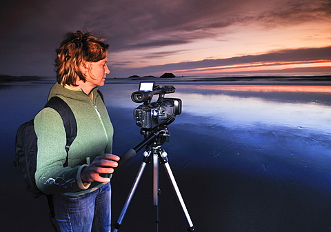 Camerawoman with movie camera filming sunset with a tripod at Meyers Creek Beach, Pistol River State Park, Oregon Coast, Oregon, USA, North America