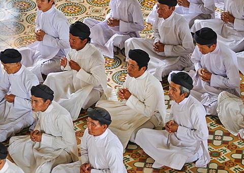 Praying devout men, ceremonial midday prayer in the Cao Dai temple, Tay Ninh, Vietnam, Asia