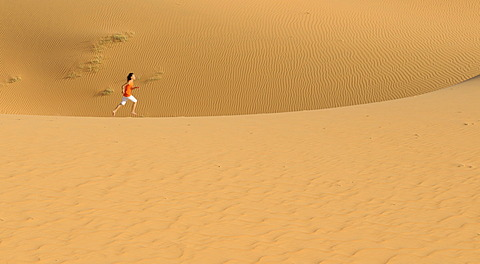 Woman running over sand dunes and structures near Mui Ne, Red Sand Dunes, Vietnam, Asia