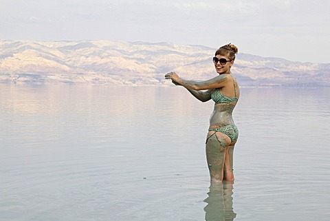 Young woman rubbing skin-soothing mud on herself, Dead Sea, West Bank, Israel, Middle East