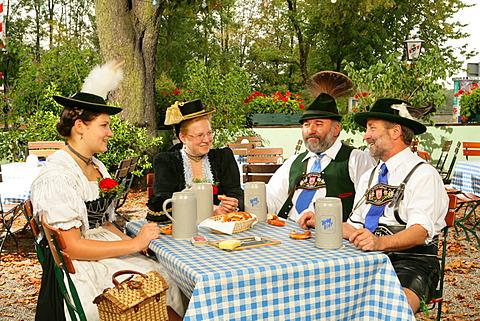 People wearing traditional costume in a beer garden, Muehldorf am Inn, Upper Bavaria, Germany, Europe