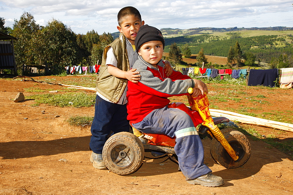 Two boys playing with a tricycle, Mapuche Indians, near Concepción, Southern Chile, Chile, South America