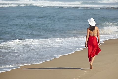 Rear view of a young woman wearing a bikini and a red sarong walking along a beach in summer, Arcachon, Aquitaine, France, Europe
