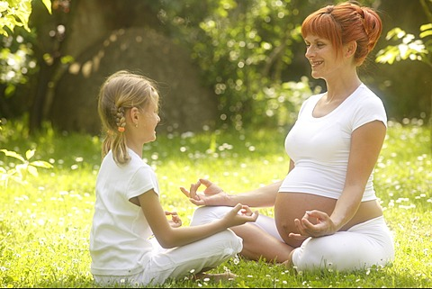 Girl and pregnant woman in yoga position in the garden