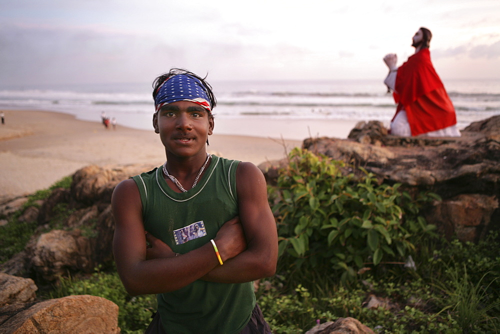  IND, India, Kerala, Trivandrum : Malabar coast, south of Trivandrum, teenager at the beach. Jesus statue at the beach, near a little pilgrimage chapel.  