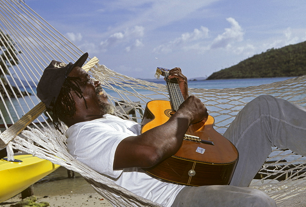 Man laying in a hammock playing the guitar, Jost Van Dyke Island, British Virgin Islands, Lesser Antilles, Caribbean