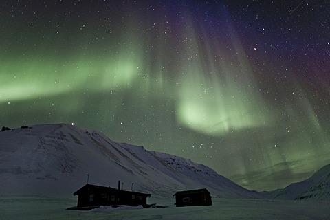Green Northern Lights, Aurora Borealis, above two small huts in a starry sky, Adventdalen, Todalen, Longyearbyen, Spitsbergen, Svalbard, Norway, Europe