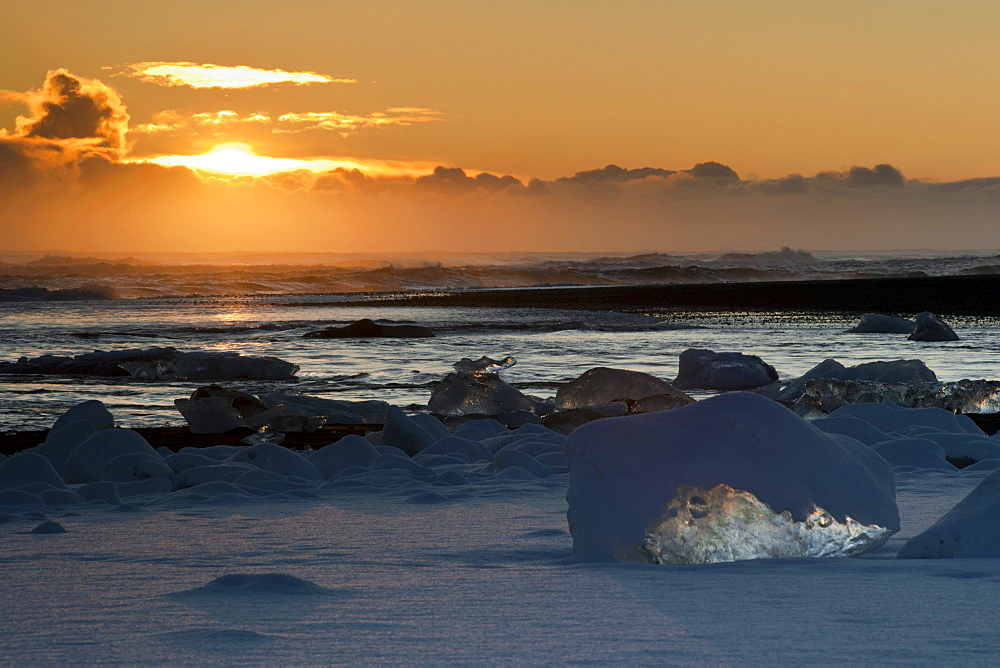 Sunset behind the snow-covered icebergs at the Atlantic coast near Joekulsárlón, Vatnajoekull National Park, Iceland, Europe