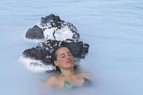Young woman enjoys bathing in hot spring, Blue Lagoon, Iceland, Europe - 832-370513