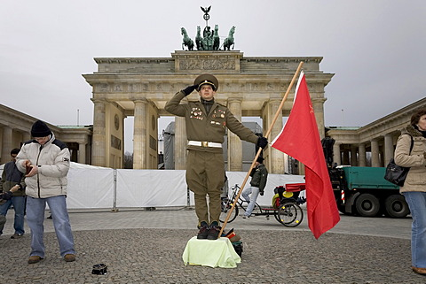 A man dressed up as a soviet army soldier poses in front of the Brandenburger Tor, Berlin