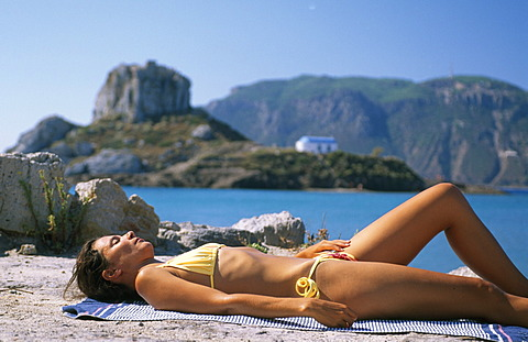 Woman sunbathing, tanning, Agios Stefanos, Kos, Dodecanese Islands, Greece