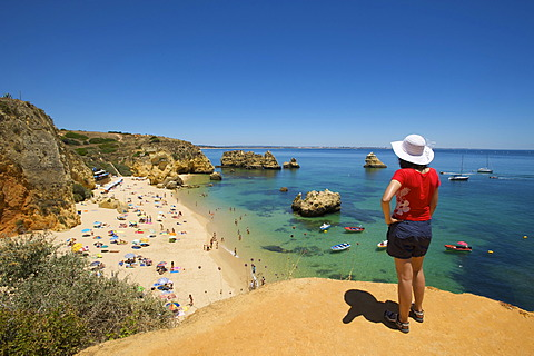 Woman overlooking Praia Dona Ana near Lagos, Algarve, Portugal, Europe