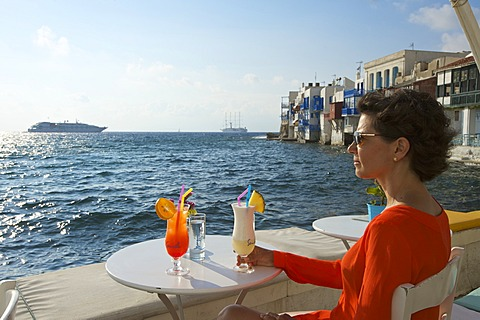 Woman enjoying a cocktail and a view over the sea, Little Venice, Mykonos Town, Mykonos, Cyclades, Greece