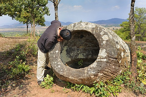 Laotian man at the Plain of Jars, prehistoric stone jars near the town of Phansavan, Laos, Southeast Asia, Asia