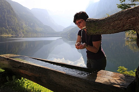 Hiker refreshing herself at a trough, Gosausee lake, Gosau, Salzkammergut region, Upper Austria, Austria, Europe