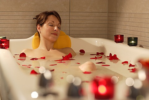 Woman, 35, relaxing in a bathtub with rose petals, Thalasso therapy in a spa resort