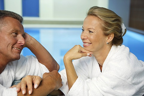 Man, 52 years, and woman, 42 years, talking and smiling, wellness