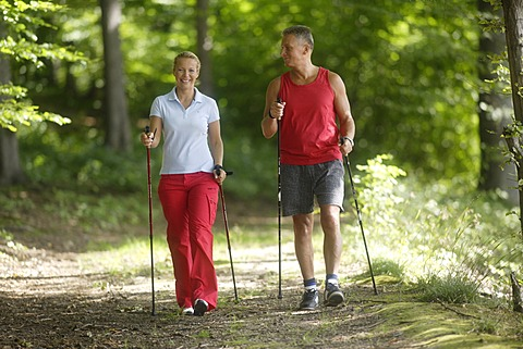 Woman, 42, and man, 52, doing Nordic Walking