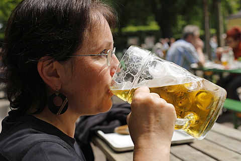 Woman drinking a litre of Spaten brand beer, Taxisgarten Beer Garden, Munich, Bavaria, Germany, Europe