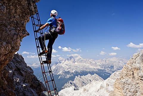 Mountain climber ascending the Via Ferrata Marino Bianchi climbing route on Cristallo di Mezzo Mountain, overlooking the Tofane Mountains, Dolomites, Belluno, Italy