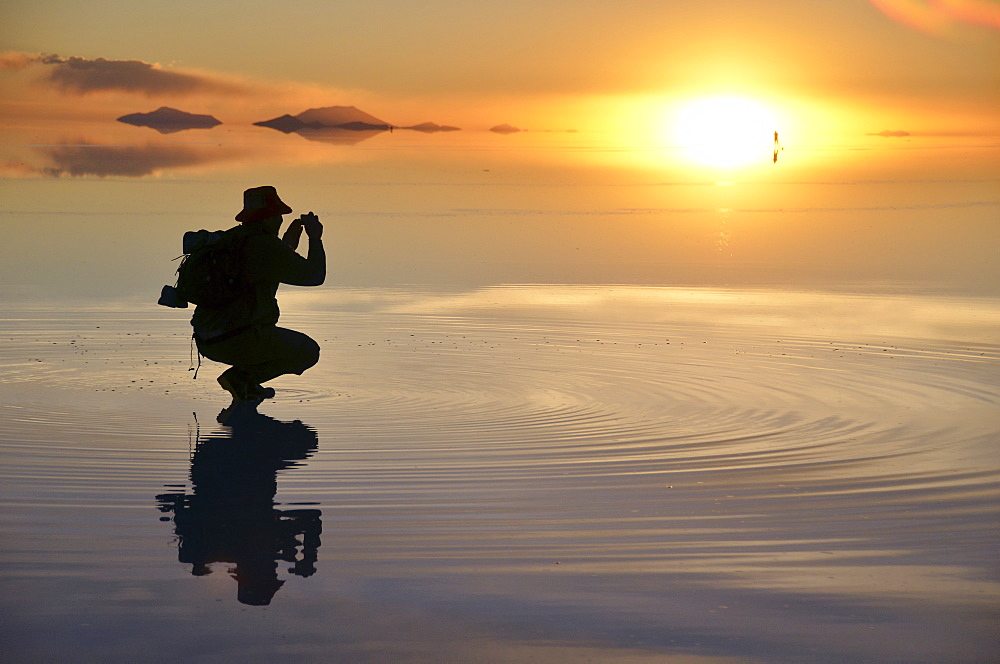 Tourist taking pictures of the sunset at the Salar de Uyuni, Uyuni, Bolivia, South America