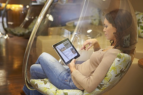 Young woman using an iPad tablet computer in a ball chair in a lounge in Munich