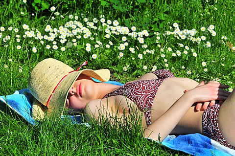 Woman wearing a bikini, sun hat, lying in the park, summer, sunbathing, sleeping