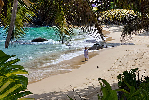 Woman walking along the beach wearing a tunic, Mahé Island, Seychelles, Indian Ocean, Africa