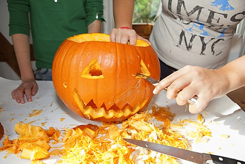 Two girls, about 14 years, carving a face into a Halloween pumpkin