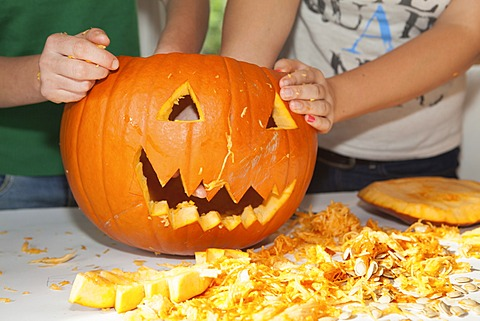 Two girls, about 14 years, carving a face into a Halloween pumpkin - 832-371482