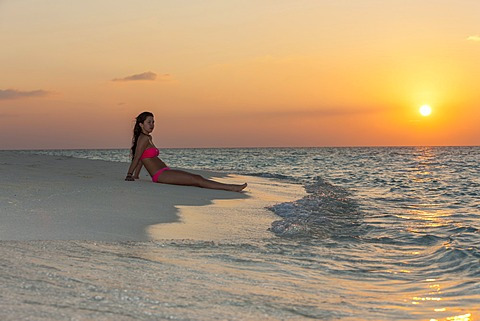 Woman sitting on the beach at sunset, Indian Ocean, Maldives - 832-371531