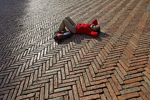 Tourist lying in the Piazza del Campo square, Siena, Tuscany region, province of Siena, Italy, Europe