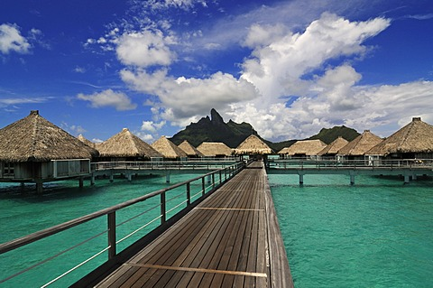Boardwalk, huts on stilts, Mt Otemanu at back, from St. Regis Bora Bora Resort, Bora Bora, Leeward Islands, Society Islands, French Polynesia, Pacific Ocean