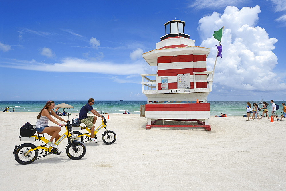 Couple riding electric bicycles, Watchtower, The Jetty, Miami Rescue Tower, South Beach, Miami, USA