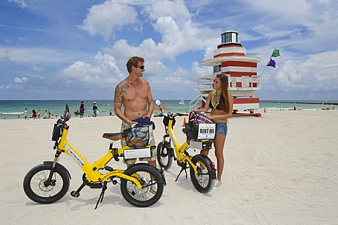 Couple riding electric bicycles, Watchtower, The Jetty, Miami Rescue Tower, South Beach, Miami, Florida, USA