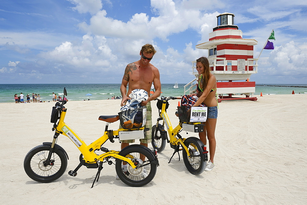 Couple with electric bicycles, Watchtower, The Jetty, Miami Rescue Tower, South Beach, Miami, Florida, USA