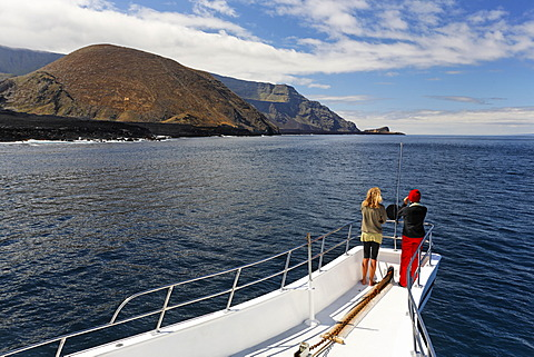Two woman standing on the bow of the ship, Reina Silvia, volcanic mountains, northern tip of Ponta de Sao Vicente, Isabella Island, Galapagos Archipelago, Ecuador, South America, Pacific Ocean